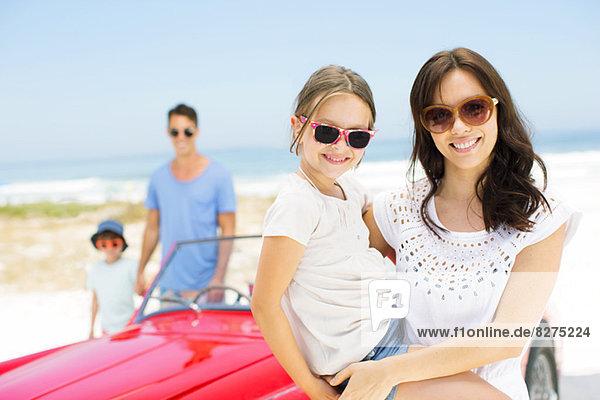 Mutter und Tochter lächeln mit dem Cabrio am Strand