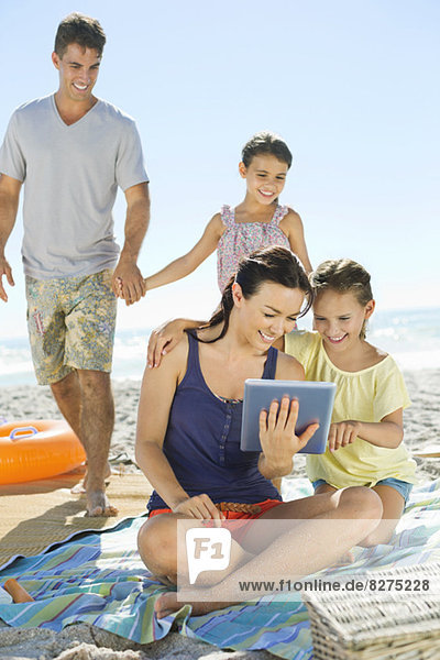 Familie mit digitalem Tablett am Strand
