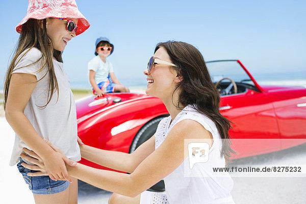 Mutter und Tochter lächeln am Strand beim Cabriolet