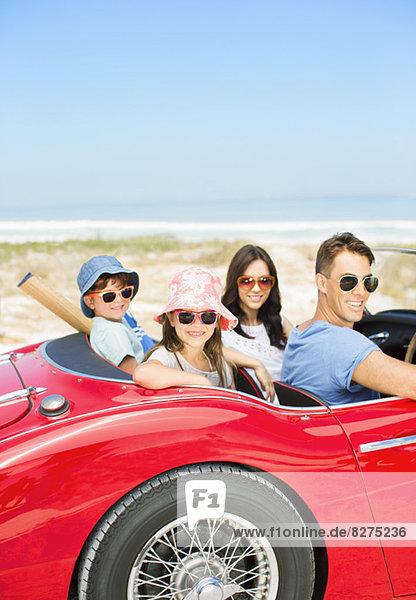 Porträt der lächelnden Familie im Cabrio am Strand