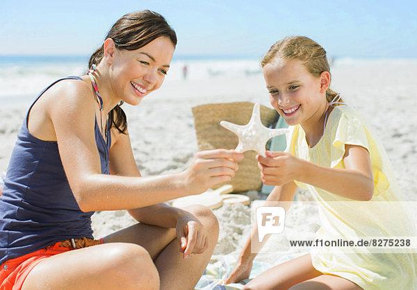 Mutter und Tochter untersuchen Seesterne am Strand