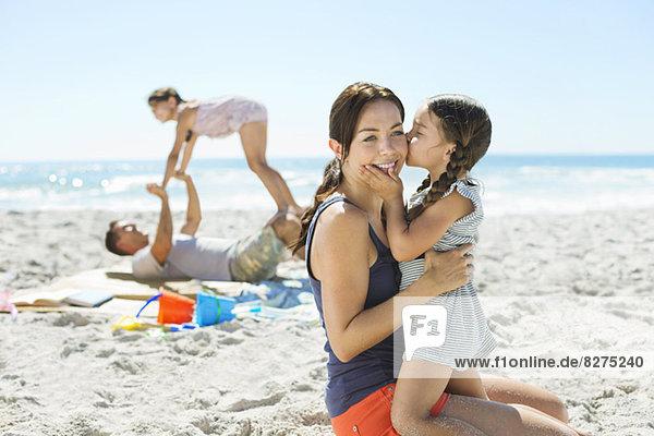 Mädchen küsst Mutters Wange am Strand