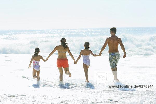 Familie beim Surfen am Strand