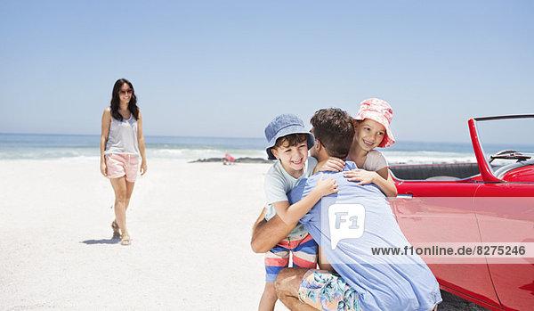 Vater umarmt Tochter und Sohn in der Nähe von Cabrio am Strand