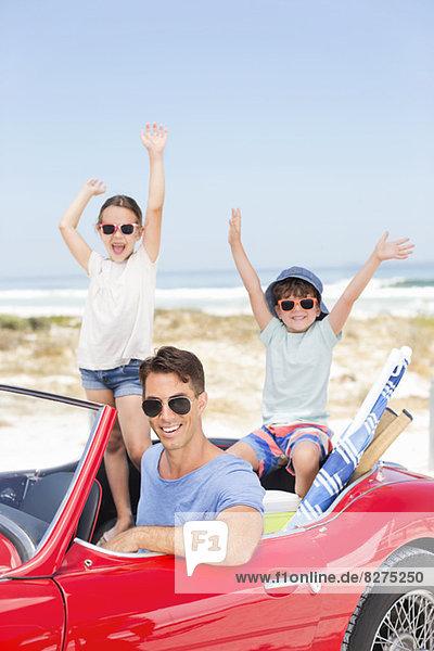 Vater und Kinder im Cabrio am Strand