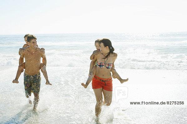 Eltern mit Töchtern huckepack beim Surfen am Strand