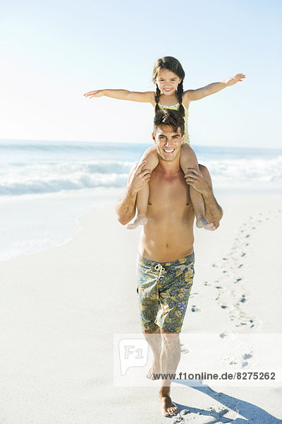Vater trägt Tochter auf Schultern am Strand