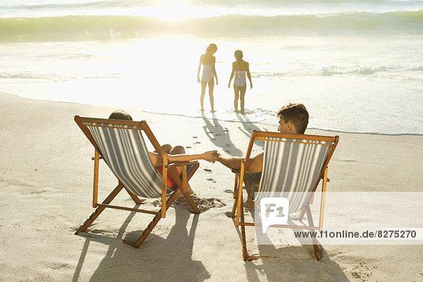 Eltern beobachten Töchter beim Surfen am Strand