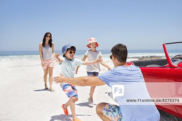 Vater  der die Kinder am Strand neben dem Cabriolet umarmt.