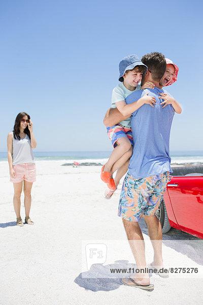 Vater umarmt Kinder am Strand