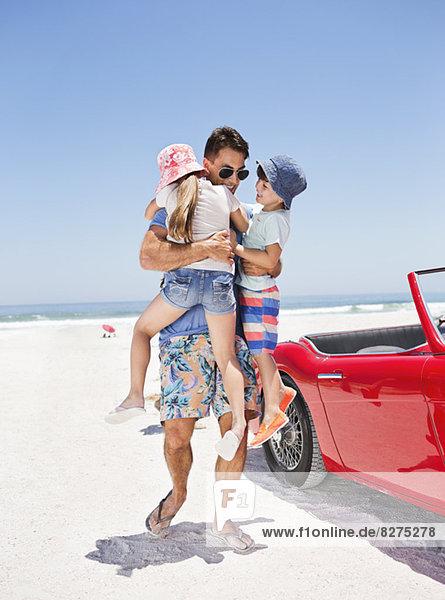 Vater umarmt Kinder am Strand neben dem Cabriolet