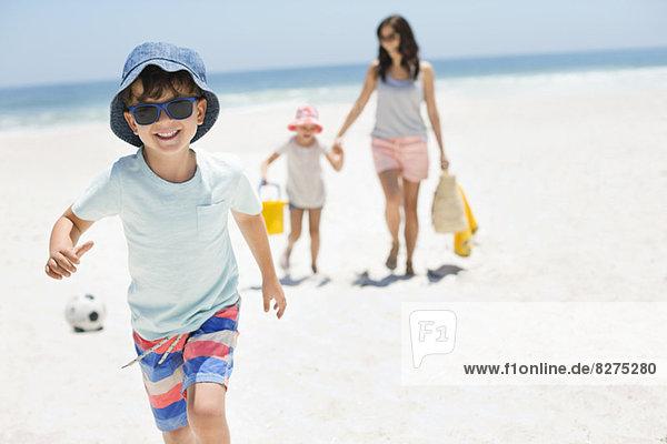 Lächelnder Junge  der am Strand rennt