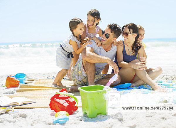 Familienumarmung auf der Decke am Strand