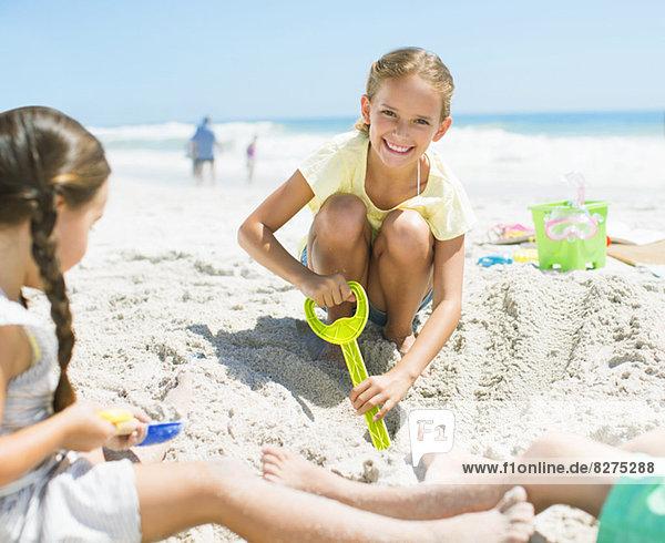 Mädchen graben im Sand am Strand