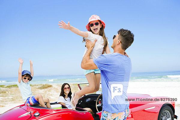 Vater hebt Tochter vom Cabrio am Strand ab