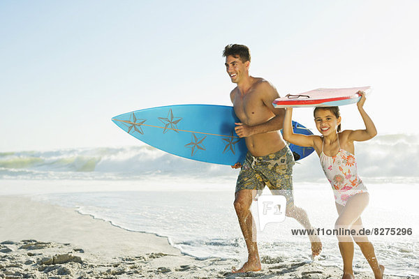 Vater und Tochter mit Surfbrett und Bodyboard am Strand