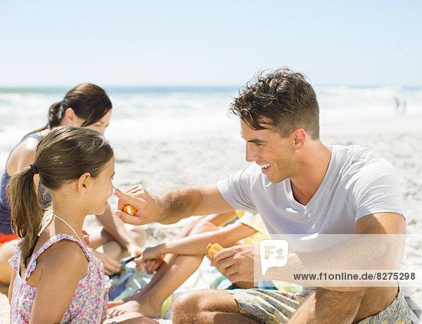 Vater reibt Sonnencreme auf die Nase der Tochter am Strand
