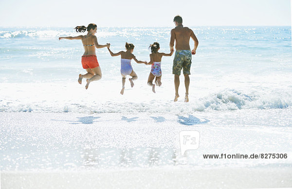 Familienspringen in der Brandung am Strand