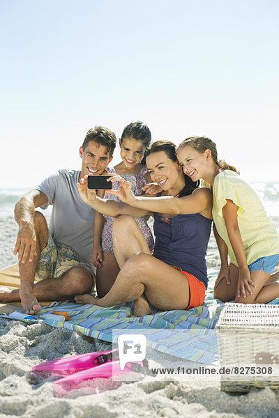 Selbstbildnis der Familie mit Fotohandy am Strand