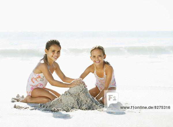 Mädchen machen Sandburg am Strand