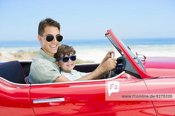 Vater und Sohn fahren Cabrio am Strand