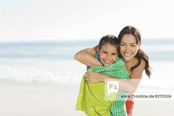 Mutter wickelt Tochter in Handtuch am Strand ein