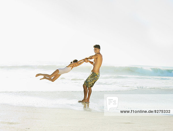 Vater schwingende Tochter am Strand