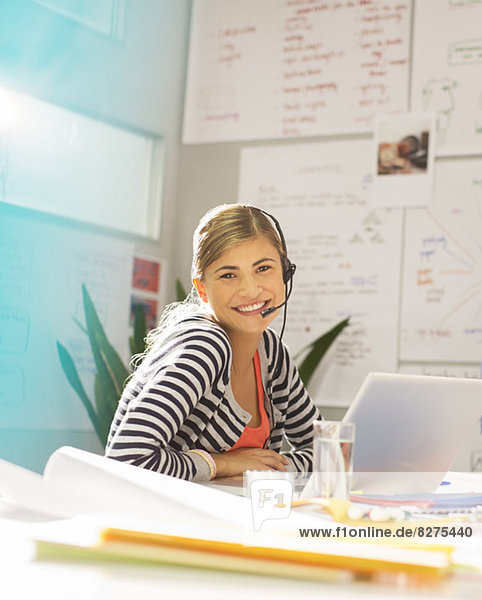 Geschäftsfrau mit Headset am Schreibtisch im Büro