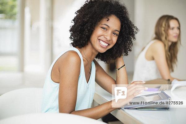 Porträt einer lächelnden Frau mit digitalem Tablett am Tisch