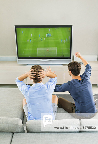 Men watching soccer game on sofa