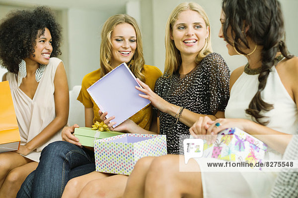 Woman opening gifts at birthday party