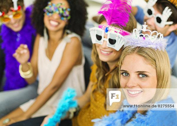 Freunde mit dekorativen Brillen und Kronen auf der Party