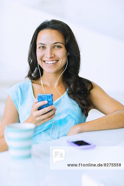 Porträt einer lächelnden Frau  die dem mp3-Player am Tisch zuhört.