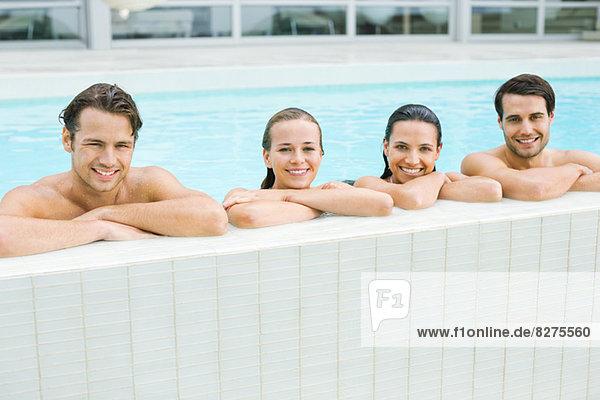 Porträt von lächelnden Freunden  die sich am Rand des Swimmingpools lehnen.