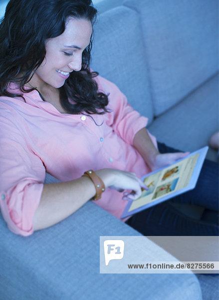 Frau mit digitalem Tablett auf dem Sofa