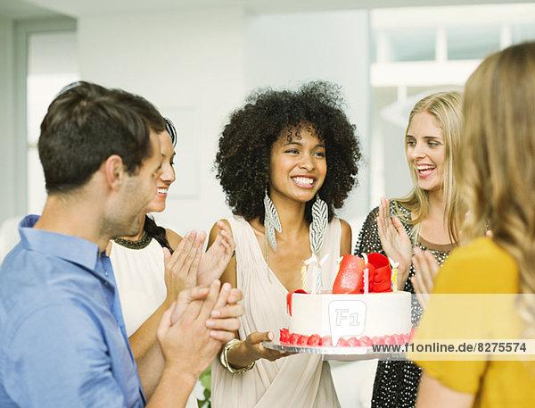 Freunde klatschen um die Frau mit Geburtstagskuchen