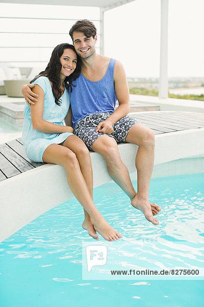 Paar Entspannung am Rande des Swimmingpools