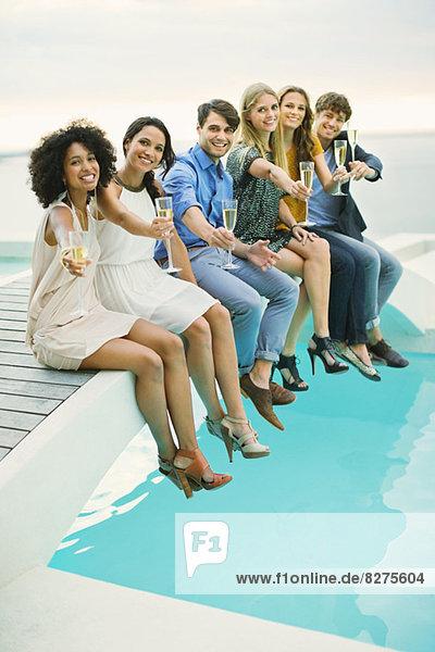 Freunde rösten Champagnerflöte auf dem Steg über dem Schwimmbad an