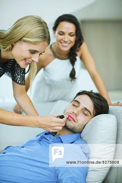 Frau beim Auftragen von Lippenstift auf den schlafenden Mann