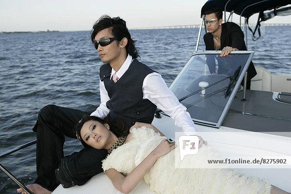 Blick auf drei Freunde auf einer Yacht.