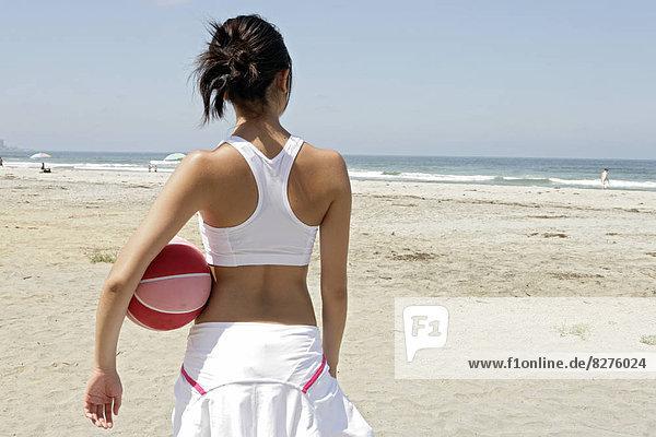 Eine Frau hält ein Gummiball und stehend auf einem Strand.