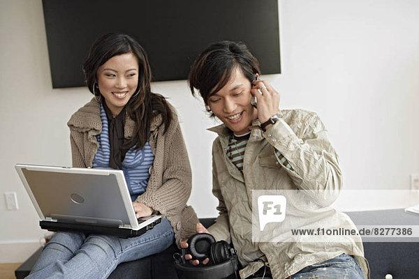 Woman working on laptop  man talking on phone