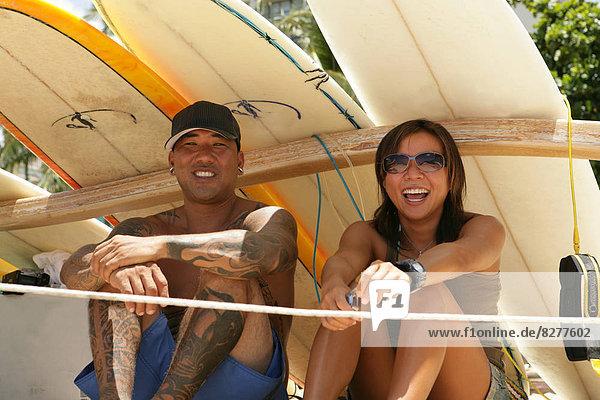 Zwei Leute sitzen unter Surfbretter