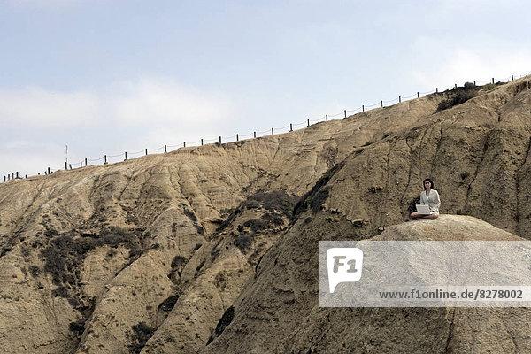 Blick auf eine Frau sitzend auf einem Felsen.