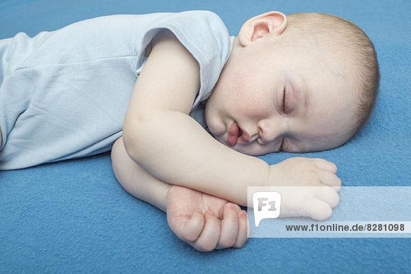 Schlafendes Baby auf blauer Decke Schlafendes Baby auf blauer Decke