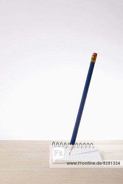 Ein Bleistift über einem Notizblock aus Millimeterpapier