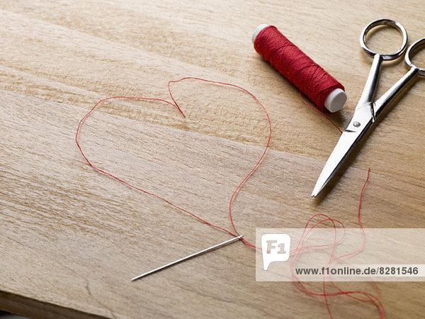 Eine Spule aus rotem Faden  Schere  Fadennadel und Faden in Form eines Herzens.