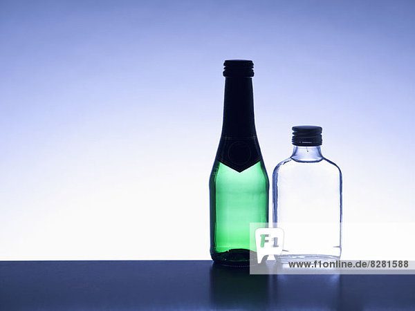 Two miniature bottles of alcohol side by side without labels  back lit