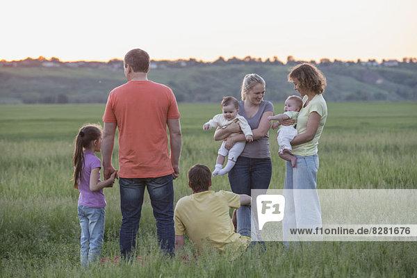 Zwei Familien  die sich auf einem Feld in ländlicher Umgebung entspannen.