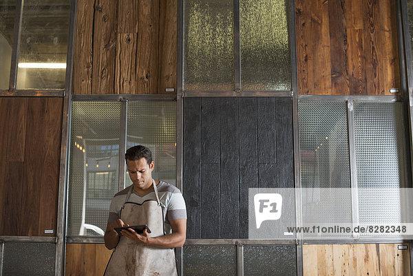Ein junger Mann in einer Werkstatt. Verwendung eines digitalen Tabletts zur Aufbewahrung von Aufzeichnungen und fotografischen Objekten.